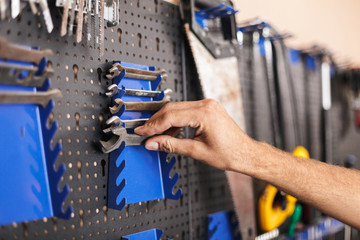 Close up man hand choosing wrenches in workshop isolated