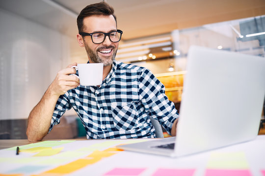 Successful designer drinking coffee, working on laptop.