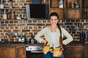 happy young repairwoman with arms akimbo standing at kitchen and looking at camera