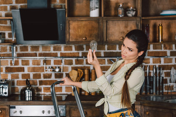 confident young repairwoman standing on stepladder and examining light bulb at kitchen