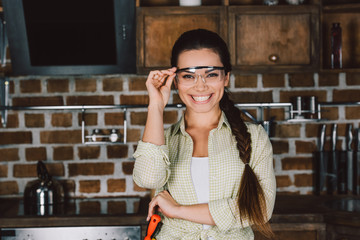 happy young repairwoman in protective glasses looking at camera
