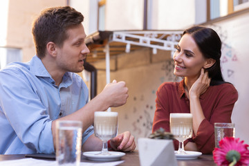 Plans for future. Handsome blonde-haired man telling his smiling loving girlfriend some plans for future