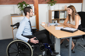 handsome disabled businessman in a wheelchair at his office in front of a beautiful young woman