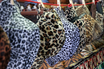 Tiger pattern fabric of cap and hat hanging on the line for sale in the local market.