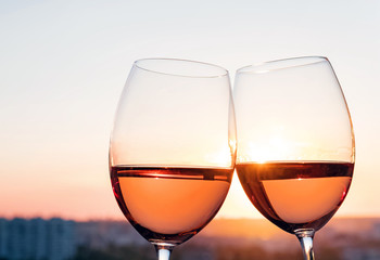 Two glasses with rose wine at sunset light.
