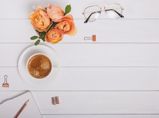 Coffee, roses and other items on the white wooden background, top view