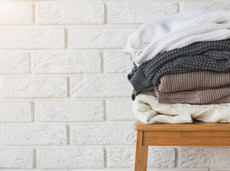 Wall Mural - Stack of winter sweaters on the white brick wall background.