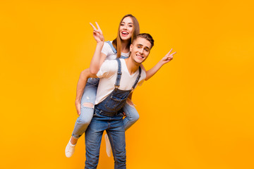 Young funny cheerful joyful couple, boyfriend piggy backing girlfriend, girl showing peace signs with her hands over yellow background, isolated Wall mural