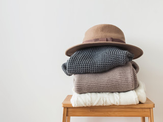 Wall Mural - Stack of warm knitted sweater and felt hat on the top of it