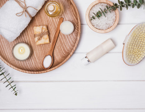 Cosmetics and accessories for body care on the white wooden table.