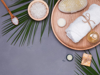 Spa still life with dry rush, white towel and tropic leaves on the grey background
