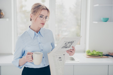 Young attractive cute adorable woman office worker wearing spectacles keeping and reading newspaper early in the morning and having a drink in kitchen