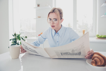 Adult adorable attractive astonished woman office executive worker wearing eyeglasses keeping in hands and reading newspaper early in the morning having a drink with croissant in light kitchen