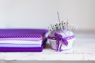 Stack of lavender and lilac fabrics and a pillow with needles for sewing, needlework, handmade on a...