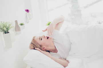 Young charming attractive adorable cute smiling blonde woman awakening in bed on white pillow covered with blanket yawning stretching in bedroom with white interior