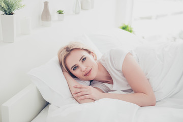 Adult caucasian cute smiling blonde woman awakening in bed on white pillow covered with blanket in bedroom with white fashionable interior. Flowers in vases