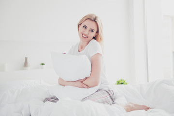 Young cute smiling blonde woman awakening in bed on white sheets and blanket hugging pillow wearing pajama enjoying in bedroom with white interior. Diet