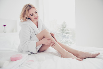 Young charming blonde adult cute mature smiling woman sitting in bed wearing white bathrobe spreading body lotion cream gel on leg after showering and taking bath, healthcare