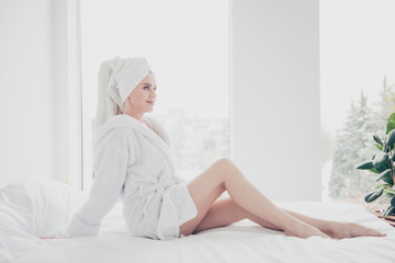 Young cute smiling woman in bed with white sheets and pillow wearing bathrobe and turban enjoying in bedroom with white interior. Healthcare