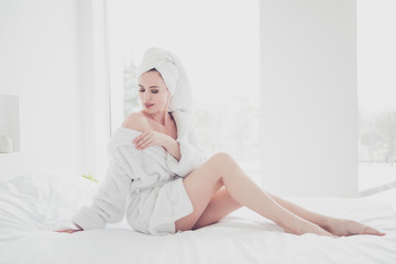 Young attractive adorable cute smiling woman in bed with white sheets and pillow wearing bathrobe and turban enjoying showing her shoulder in bedroom with white interior. Healthcare