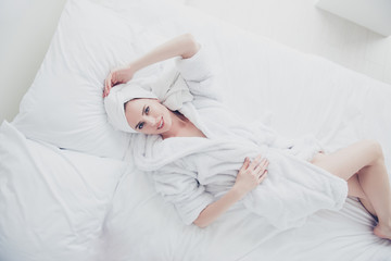Young cute adorable attractive smiling woman lying in bed on white sheets and pillow wearing bathrobe and turban enjoying touching head with one arm. Top above high angle veiw