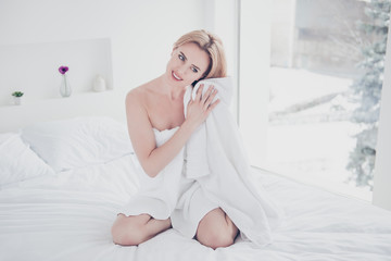 Young cute adorable attractive beautiful smiling woman sitting on bed on white sheets with pillows wearing towel after bath drying her hair with towel