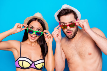 Photo of two excited and wondered people with open mouths dressed in swimsuits and hatwear, they are touching colorful glasses, isolated on blue background. Concept of large sales and discount