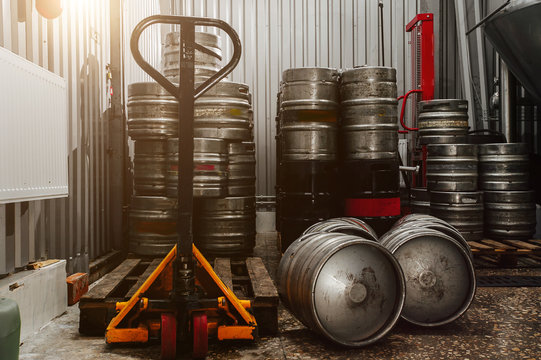 Many metal beer keg stand in a warehouse of brewery. Time to delivery. Beer kegs on the production line in the factory