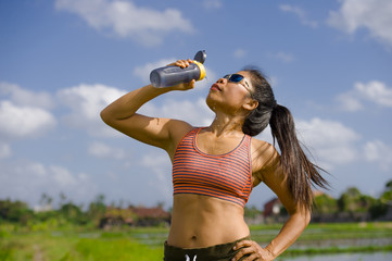 attractive and fit Asian runner woman holding isotonic bottle drinking water after training and running series workout at outdoors track in green field