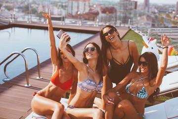 Four young women in a penthouse near the pool doing selfie in a bikini