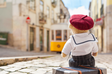 Travel to Lisbon / Back of cute teddy bear wearing sailor shirt and beret hat at street of Lisbon (Portugal), sit on his suitcase, old tramway at the background