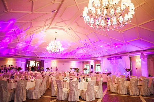 photo interior is a refined banquet hall with purple and pink light