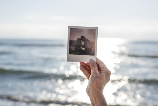 Old lady holding a photograph at the beach