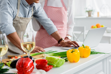 cropped image of senior couple cooking at kitchen and using laptop