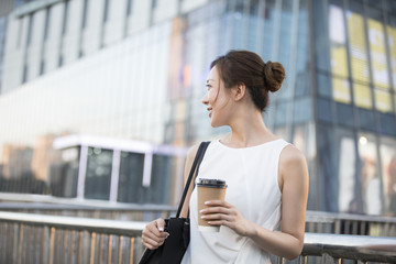 Confident young Chinese businesswoman holding  a cup of coffee