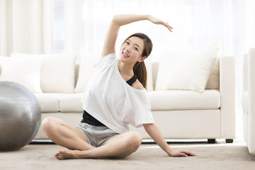 Young Chinese woman practicing yoga at home