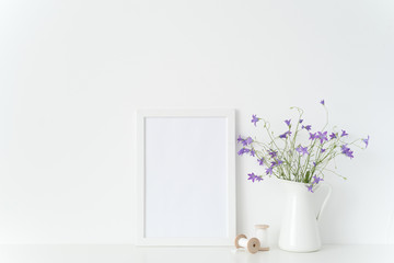 Cute white portrait frame mockup with summtr lilac wild flowers in jug, coils and tapes near wall on white background. Empty frame mock up for presentation design. Template framing for interior art.