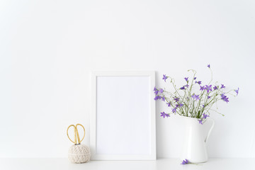 Vintage white portrait frame mockup with summer lilac flowers in vase near white wall. Empty frame mock up for presentation design. Template framing for modern art.