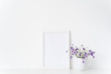Minimal white portrait a4 frame mockup with wild lilac flowers in mug near white wall. Empty frame mock up for presentation design. Template framing for modern art.