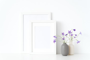 White portrait a4, a5 frame mockup with wild sprihg bellflowers in vases near wall on white background. Empty frame mock up for presentation design. Template framing for modern stylish art.