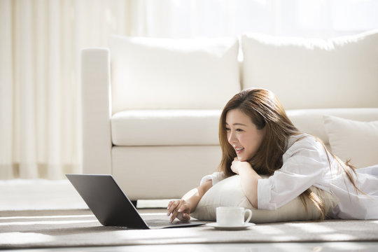 Cheerful young Chinese woman using laptop at home