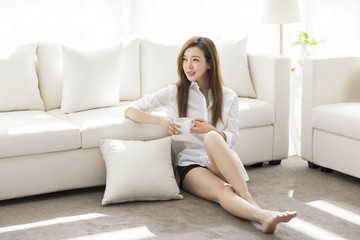 Cheerful young Chinese woman drinking coffee at home