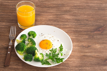 Aluminium Prints Egg Fried eggs with broccoli and greens. Delicious homemade breakfast. On a wooden table, selective focus