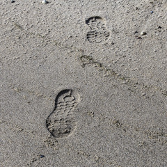 Photo of left human footprint on sand with amazing nature sun lightning. Can see footprint up and down in one photo like 3D.