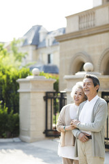 Cheerful senior Chinese couple standing in front of their villa