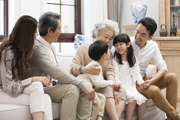 Happy Chinese family sitting on sofa