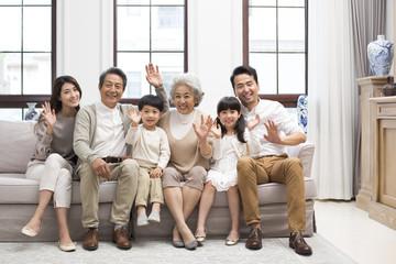 Happy Chinese family waving on sofa