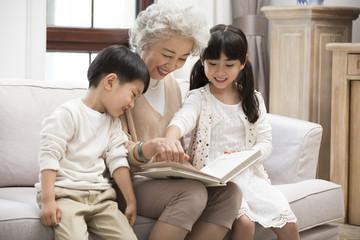Cheerful Chinese grandmother and grandchildren looking at photo album
