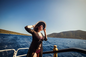 Beautiful girl in hat relaxing on the boat and looking at the island. Travelling vocation tour in Turkey