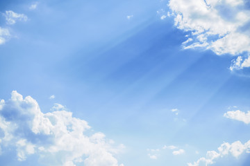 The blue sky with the rays of the sun piercing through the clouds